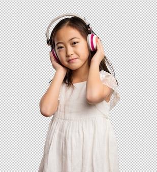 Chinesisches kleines mädchen, das auf die kopfhörer hört