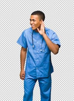Chirurg doktormann, der auf etwas hört, indem er hand auf das ohr setzt