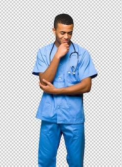 Chirurg doktormann, der unten mit der hand auf dem kinn schaut