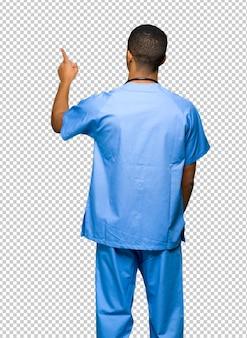 Chirurg doktormann, der zurück mit dem zeigefinger zeigt
