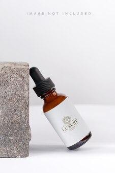 Closeup serum-essenz in glasmodellflasche auf steinhintergrund isoliertes hautpflegeöl