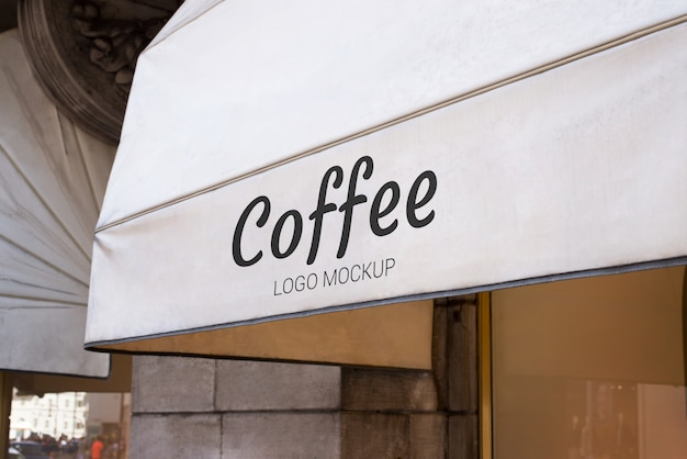 Coffeeshop-logo-modell auf weißer markise. traditioneller blick von weißweiß vor fenster gesetzt