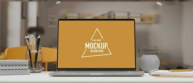 Computer-laptop mit mock-up-bildschirm auf dem arbeitstisch mit schreibwaren