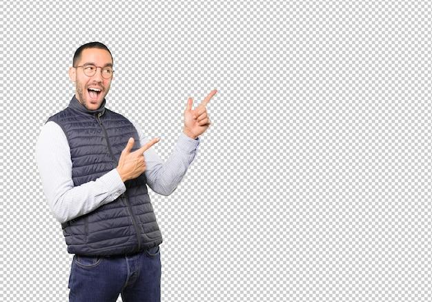 Cooler junger mann, der mit seinen fingern zeigt
