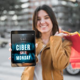 Cyber montag-modell mit frau, die tablette hält