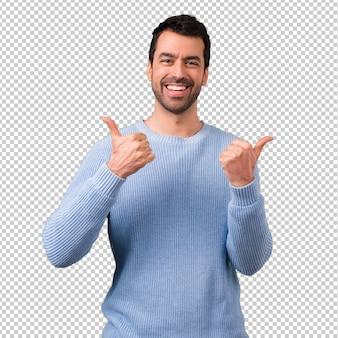 Das geben des gutaussehenden mannes daumen up geste und das lächeln