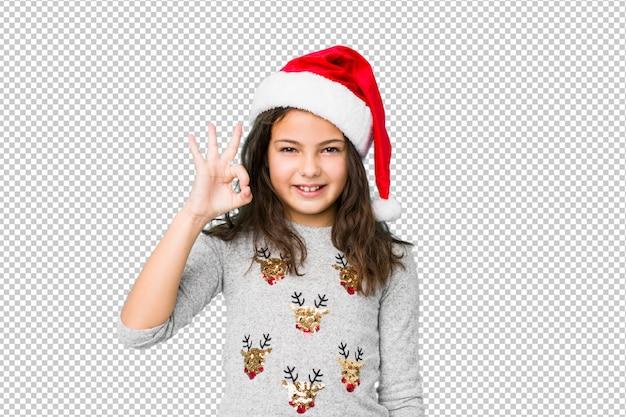 Das kleine mädchen, das weihnachtstag feiert, blinzelt ein auge und hält eine okaygeste mit der hand.