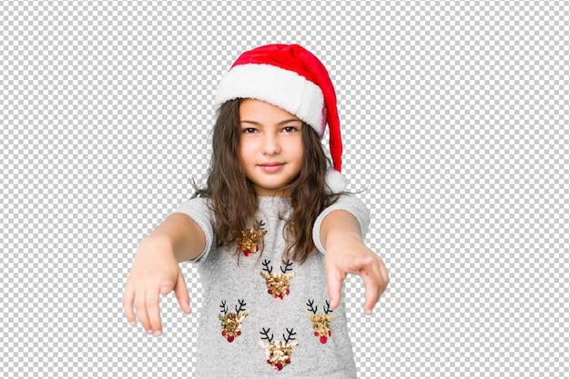 Das kleine mädchen, das weihnachtstag feiert, freundlich lächelt, zeigend auf front.