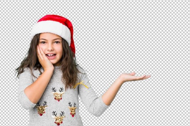 Das kleine mädchen, das weihnachtstag feiert, hält kopienraum auf einer palme, hält hand über backe. erstaunt und entzückt.