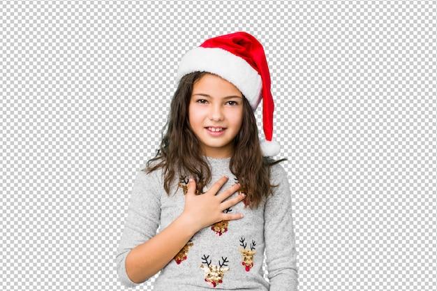 Das kleine mädchen, das weihnachtstag feiert, lacht laut, hand auf kasten halten.