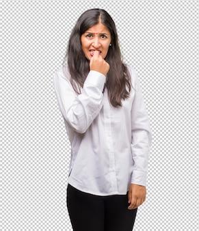 Das porträt einer jungen indischen frau, die nervös, ängstlich und voller angst um die zukunft nägel beißt, verspürt panik und stress