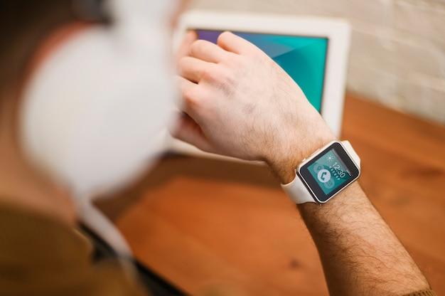 Defokussierter mann, der von zu hause aus arbeitet, während er smartwatch betrachtet
