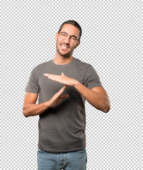 Der betonte junge mann, der eine zeit heraus bildet, gestikulieren mit seinen händen