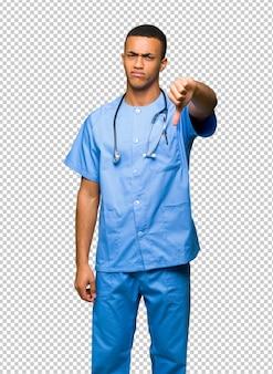 Der chirurgdoktormann, der unten daumen zeigt, unterzeichnen mit negativem ausdruck