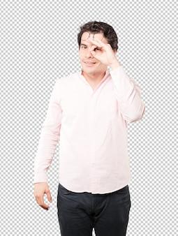 Der glückliche junge mann, der seine hände verwendet, mögen ferngläser