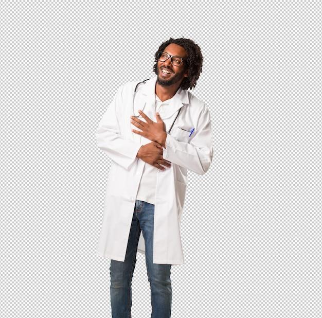 Der hübsche afroamerikanerarzt, der spaß lacht und hat, entspannt und nett ist, fühlt sich überzeugt und erfolgreich