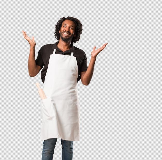 Der hübsche afroamerikanerbäcker, der spaß lacht und hat, entspannt und nett ist, fühlt sich überzeugt und erfolgreich