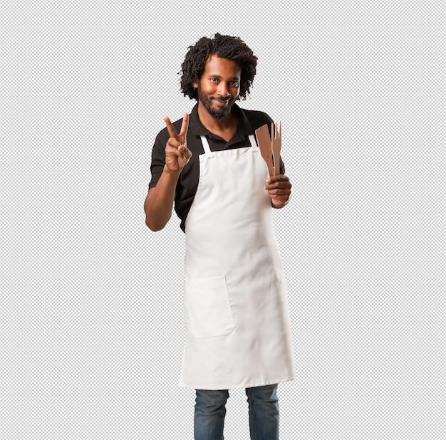 Der hübsche afroamerikanerbäckerspaß und glücklich, positiv und natürlich, macht eine geste vom sieg, friedenskonzept