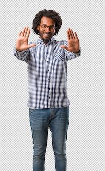 Der hübsche geschäftsafroamerikanermann, der ernst und entschlossen ist, hand in front setzend, stoppen geste, verweigern konzept