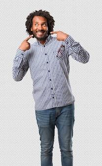 Der hübsche geschäftsafroamerikanermann, der lächelt und zeigt mund, konzept von perfekten zähnen, weiße zähne, hat eine nette und gemütliche haltung