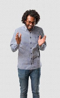 Der hübsche geschäftsafroamerikanermann, der spaß lacht und hat, entspannt und nett ist, fühlt sich überzeugt und erfolgreich