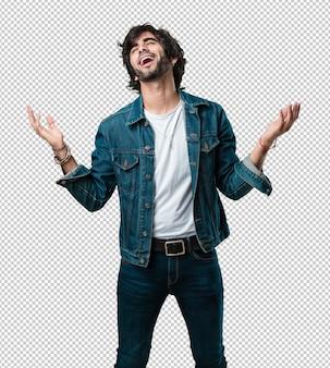 Der junge gutaussehende mann, der spaß lacht und hat, entspannt und fröhlich ist, fühlt sich überzeugt und erfolgreich