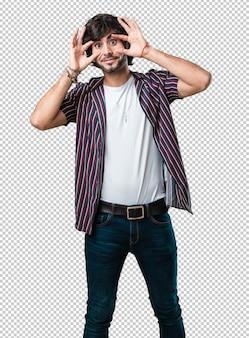 Der junge gutaussehende mann, der überrascht und entsetzt ist und mit großen augen, aufgeregt durch ein angebot oder durch einen neuen job, schaut, gewinnen