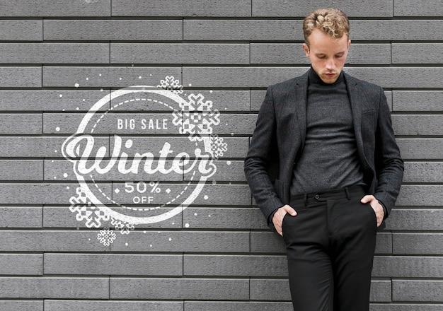 Der junge mann, der winterschlussverkauf fördert, zählt