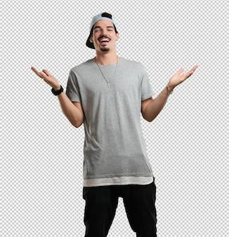 Der junge rapper, der lacht und spaß hat, entspannt und fröhlich ist, fühlt sich sicher und erfolgreich