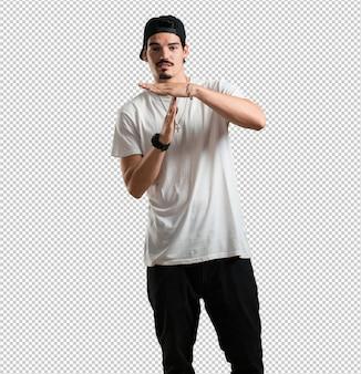Der junge rapper-mann, der müde und gelangweilt ist und eine timeout-geste tut, muss wegen arbeit s aufhören