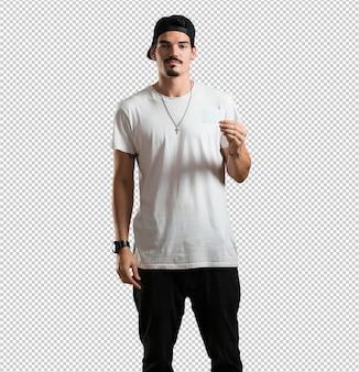 Der junge rappermann, der überzeugt lächelt und eine visitenkarte anbietet, hat ein blühendes geschäft