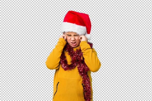 Der kleine junge, der den weihnachtstag trägt einen sankt-hut feiert, lokalisierte bedeckungsohren mit den händen.