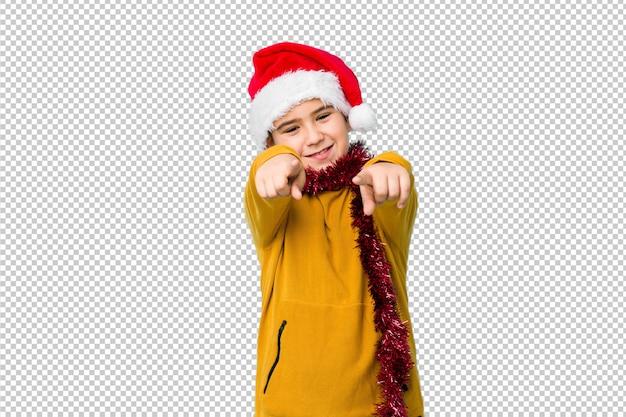 Der kleine junge, der den weihnachtstag trägt einen sankt-hut feiert, lokalisierte das freundliche lächeln, das auf front zeigt.