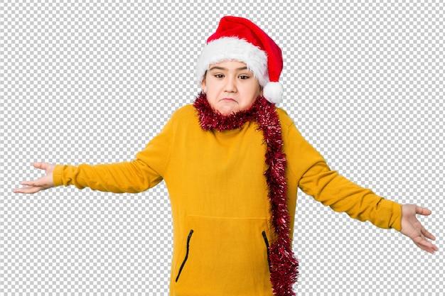 Der kleine junge, der den weihnachtstag trägt einen sankt-hut feiert, lokalisierte das zweifeln und die schultern zuckend, wenn er geste in frage stellte.