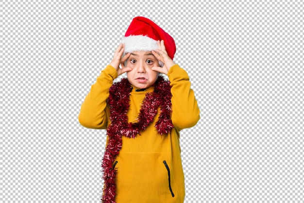 Der kleine junge, der den weihnachtstag trägt einen sankt-hut hält augen feiert, öffnete sich, um eine erfolgschance zu finden.