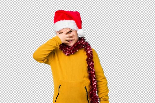 Der kleine junge, der weihnachtstag einen sankt-hut tragend feiert, lokalisierte blinken an der kamera durch finger, verlegenes bedeckungsgesicht.