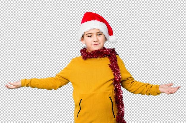 Der kleine junge, der weihnachtstag einen sankt-hut tragend feiert, lokalisierte das zeigen eines willkommenen ausdrucks.