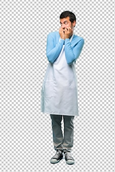 Der mann, der eine schürze trägt, ist ein bisschen nervös und verängstigt, die hände in den mund zu setzen