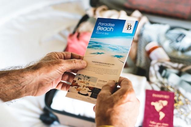 Der mann, der strand hält, reist broschüre