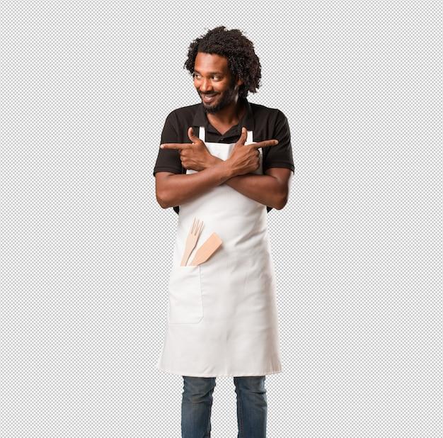 Der verwirrte und zweifelhafte mann des hübschen afroamerikanerbäckers, entscheiden zwischen zwei wahlen, konzept der unentschlossenheit