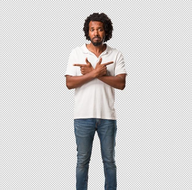 Der verwirrte und zweifelhafte mann des hübschen afroamerikaners, entscheiden zwischen zwei wahlen, konzept der unentschlossenheit
