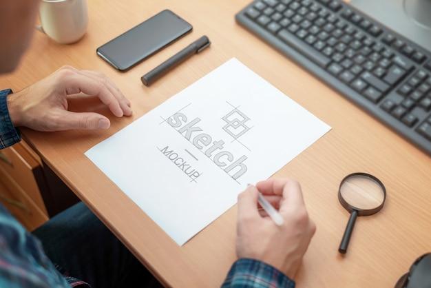 Designer-skizzenmodell. papier auf dem schreibtisch. blick über die schulter. computertastatur, telefon, stift, kaffeetasse, lupe daneben