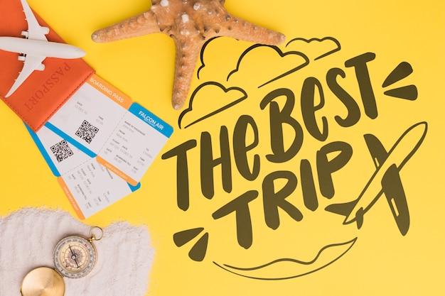 Die beste reise, schriftzug mit seestern, flugticket und kompass