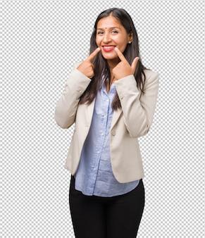 Die junge indische frau des geschäfts lächelt und zeigt mund, konzept von perfekten zähnen, weiße zähne, hat eine nette und gemütliche haltung