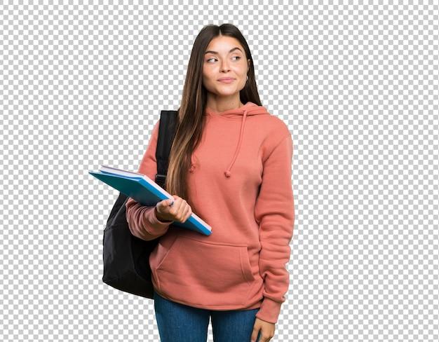 Die junge studentenfrau, die die notizbücher machen zweifel hält, gestikulieren das schauen der seite