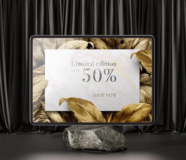 Digitales tablet mit goldenen blättern auf marmor