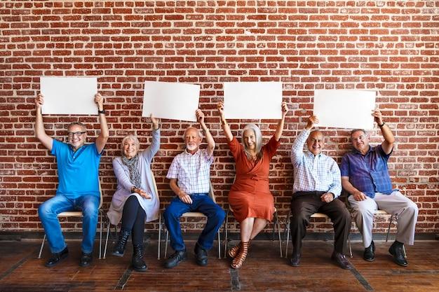Diverse ältere menschen, die ein leeres postermodell halten