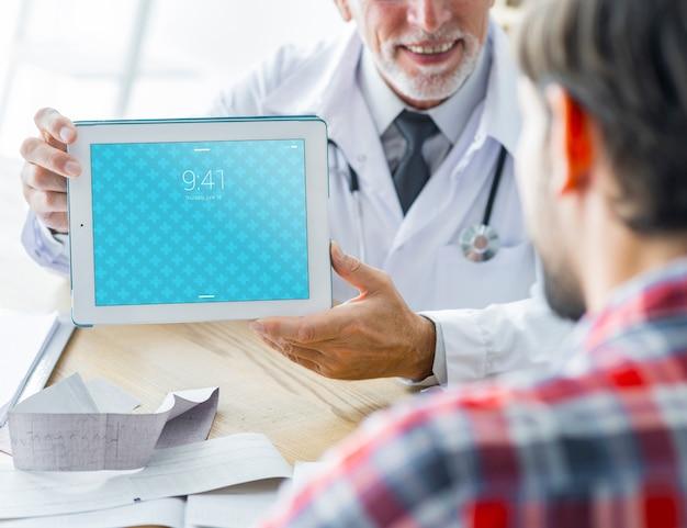 Doktor, der dem patienten tablette zeigt