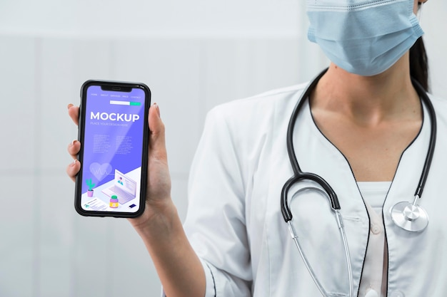 Doktor mit gesichtsmaske, die telefonmodell hält