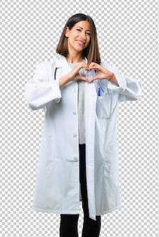 Doktorfrau mit dem stethoskop, das ein herz mit seinen händen macht